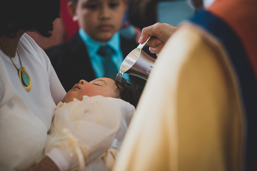 Bebé es rociado con agua bendita en la cabeza, parte del reportaje del bautizo en Berlín de Mateo.