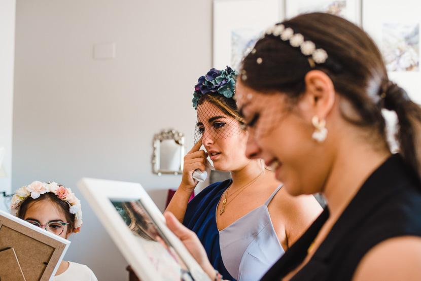 Dama de honor llorando en un momento emotivo al recibir un regalo de la novia durante los preparativos fotografiado por Bodas con Arte