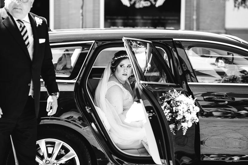 Novia bajandose del coche para dirigirse a la ceremonia de su boda en la iglesia del cachorro fotografiado por Bodas con Arte