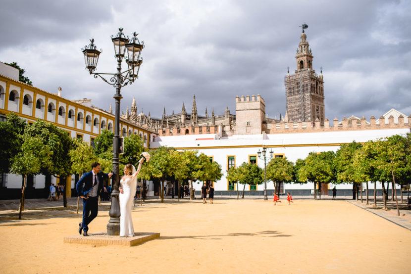 Pareja de recien casados posando en el patio de los naranjos con la Giralda de fondo. Foto por Bodas con Arte, Fotógrafos de bodas en Sevilla