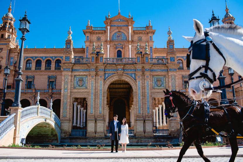 Pareja de Surcoreanos posando en la plaza de España. Foto por Bodas con Arte, Fotógrafos de bodas en Sevilla