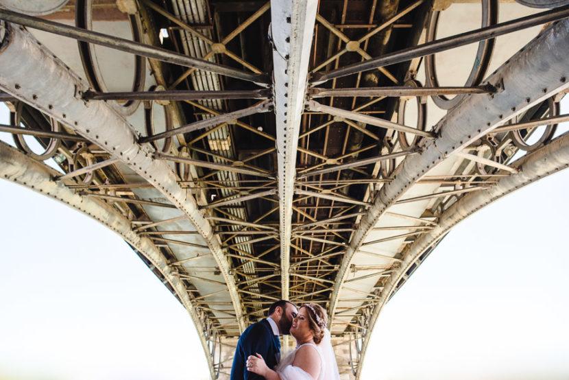 Pareja de novios besandose bajo el puente de Isabel II (Puente de Triana). Foto por Bodas con Arte, Fotógrafos de bodas en Sevilla