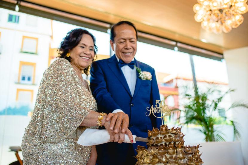 Pareja de ancianos cortando la tarta por la celebración de su boda de oro (50 años de casados). Foto por Bodas con Arte, Fotógrafos de bodas en Sevilla
