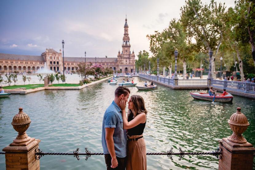 Pareja norteamericana posando en el estanque de la plaza de españa durante su reportaje de compromiso. Foto por Bodas con Arte, Fotógrafos de bodas en Sevilla