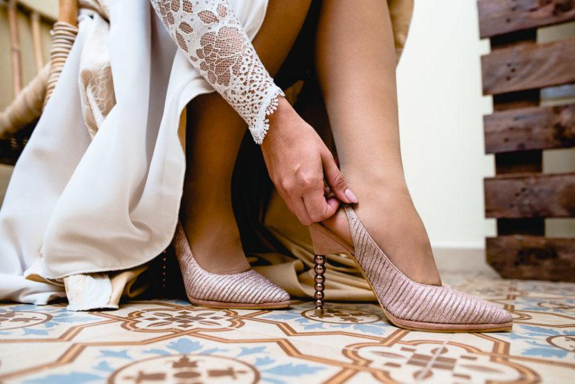 Novia poniendose sus zapatos de tacón en sus preparativos de boda. Foto por Bodas con Arte, Fotógrafos de bodas en Sevilla